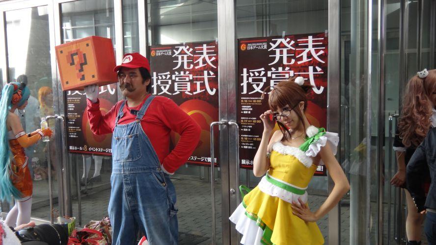 Super Mario é tão apaixonado pela princesa Peach que nem reparou na mocinha fazendo pose logo ao lado dele