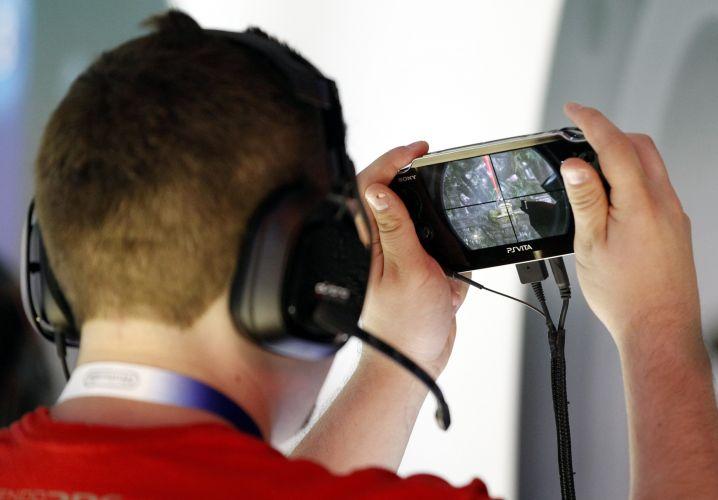 Visitante da E3 testa o PS Vita, novo portátil da Sony mostrado no evento