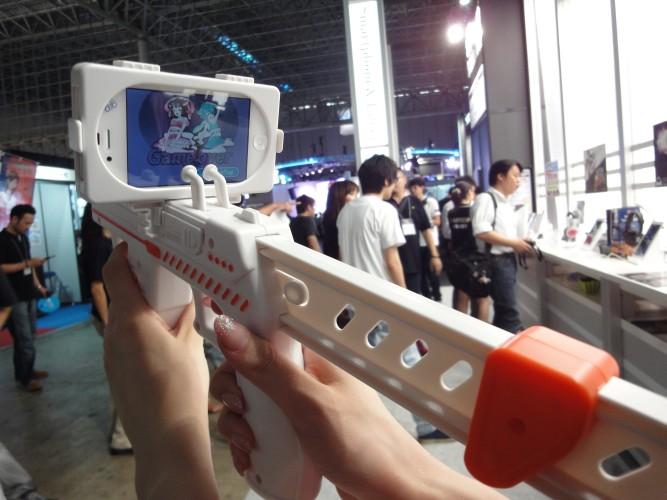 Promotora demonstra acessório em forma de arma para ser usado em jogos para celulares. E nós que achávamos que o intuito dos smartphones era poder levar seus jogos no bolso