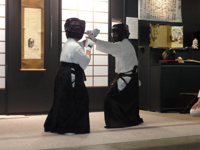 Demonstração de equipamentos de artes marciais com sensores embutidos. Assim, a armadura brilha quando é atingida, sinalizando o toque do golpe