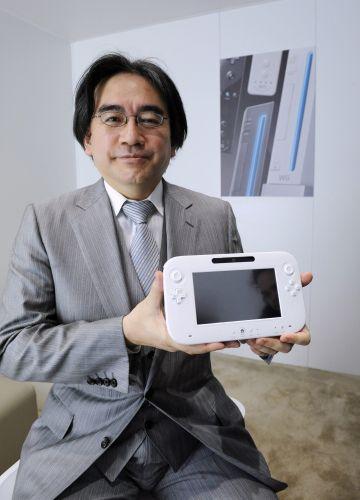 O presidente da Nintendo Satoru Iwata posa ao lado do controle do Wii U