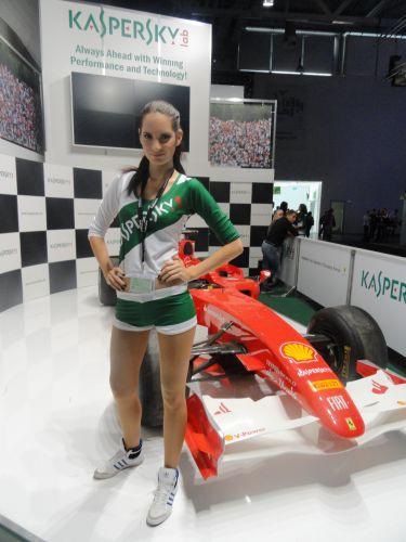 Promotora posando ao lado de uma Ferrari no estande da Kaspersky