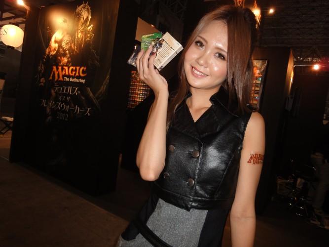 Promotora capricha no sorriso para alardear as qualidade do game baseado no jogo de cartas